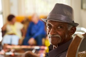 Older person sitting in a chair looking at the camera with friends in the background.