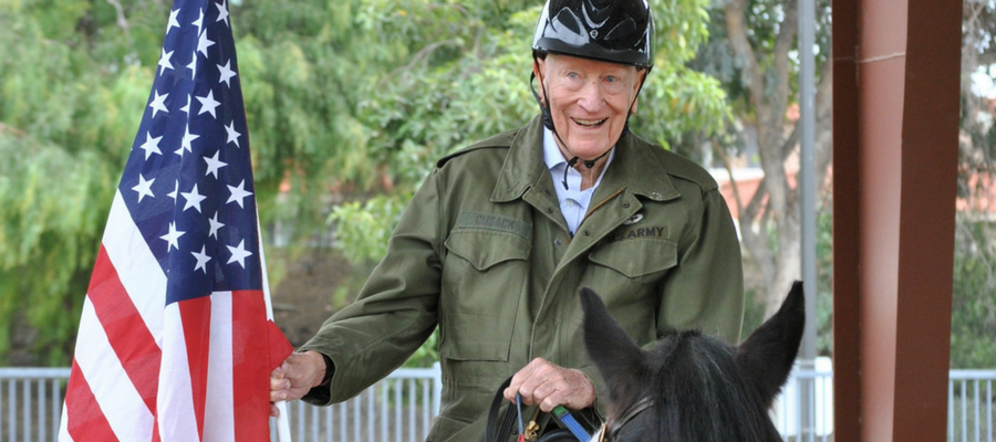 Older person holding the United States flag and riding a horse.