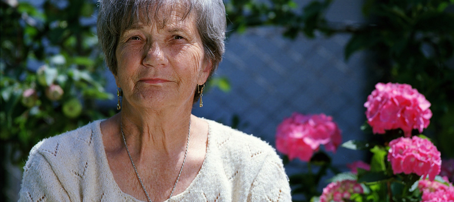 Older person looking at the camera with flowers in the background.